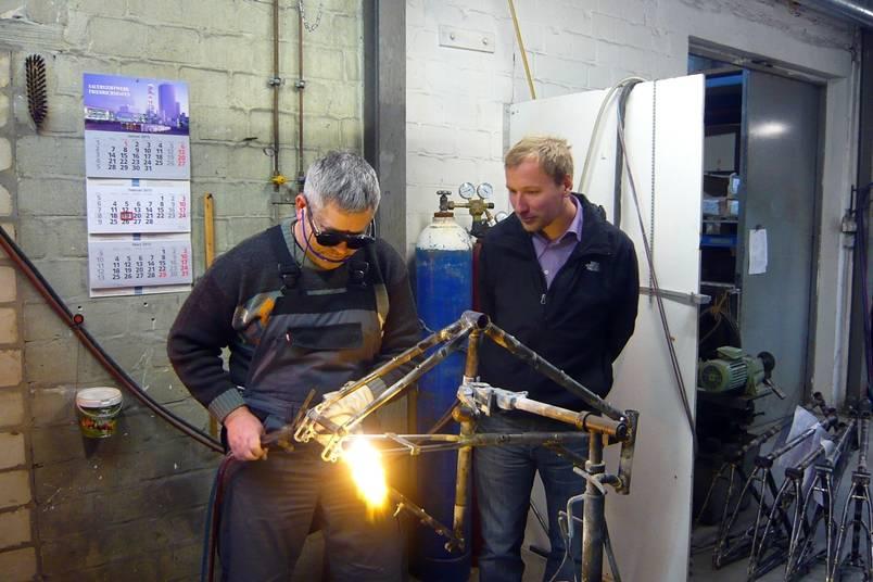 Christian Starck schaut den Fahrradrahmenbauer über die Schulter
